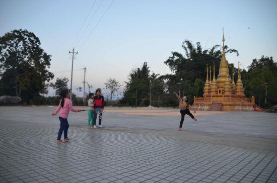 图为震后恢复重建的傣族村庄,儿童在活动广场上运动。