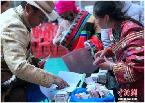 2017年12月2日,青海省海西蒙古族藏族自治州天峻县生态畜牧业合作社联合社的分红大会总分红金额达1304万元,藏族牧民用袋装现金。孙睿 摄