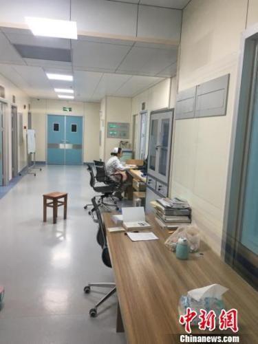护士刘丹边写病例边抱孩子哄睡觉。砚山县委宣传部供图