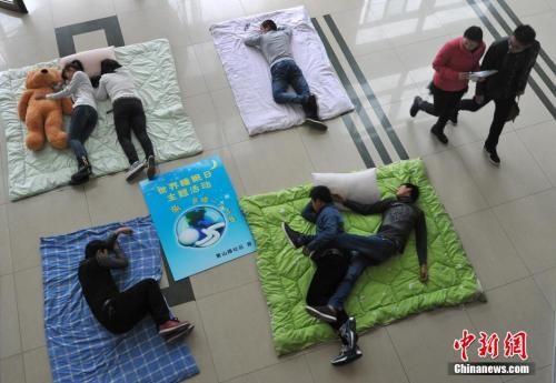 """资料图:2015年3月20日,合肥学院的学生们举办""""晒""""睡姿大赛,迎接世界睡眠日的到来。 中新社发 韩苏原 摄"""