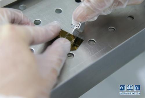 4月11日,复旦大学微电子学院教授张卫、周鹏团队成员刘春森在实验室内对硅片进行切割。 新华社记者 丁汀 摄 图片来源:新华网