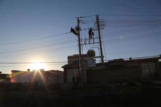 夕阳下施工人员在拉线、紧线 朱昆林摄