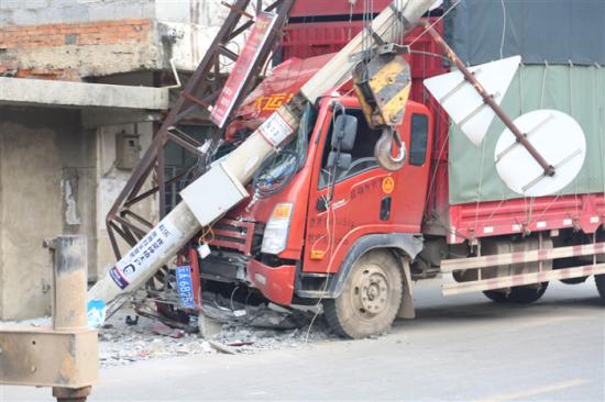 图为公路边的电杆经常被车辆撞断,造成大面积停电