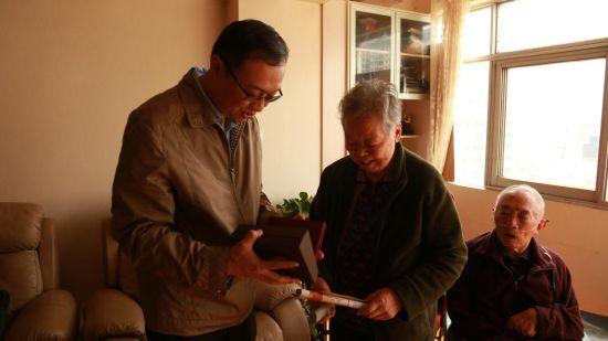 五华区总工会领导向王老师送去珍贵的纪念章。