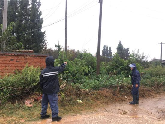 工作人员冒雨巡视线路故障中