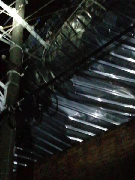 一块彩钢瓦被大风吹到高压线上导致停电