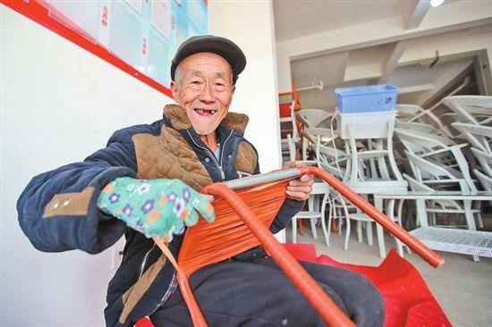 73岁的赵英贵在扶贫车间编凳子,编一个凳子有6元钱收入。