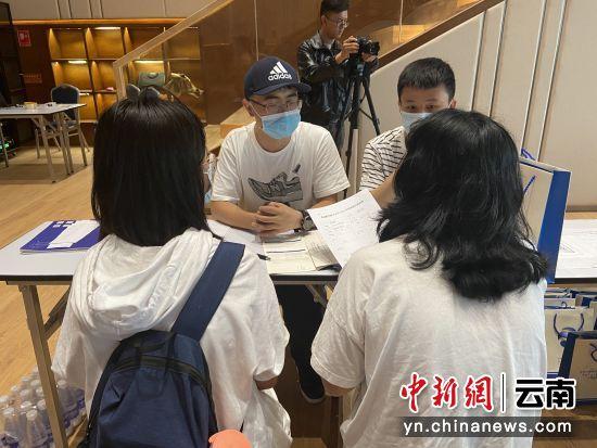 学生和家长正在现场咨询招生政策。 陈天宇 摄