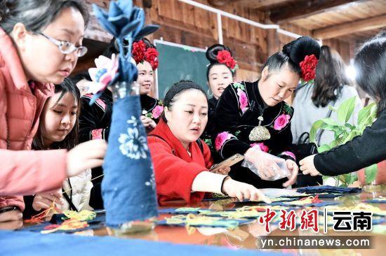 图为游客在龙塘村非遗工坊和绣娘学苗绣