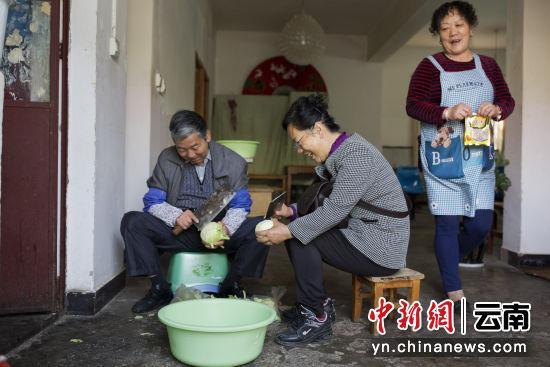图为陈桂仙(右二)为爱心小饭桌准备饭菜