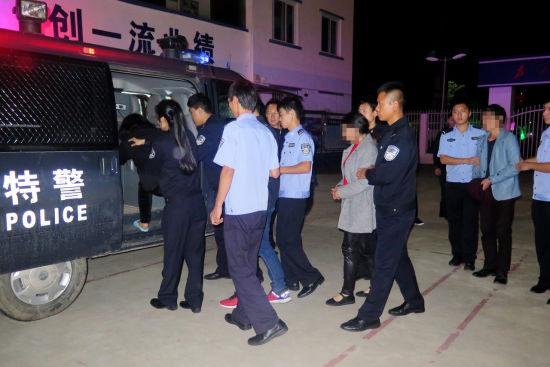 图为民警押解犯罪嫌疑人。