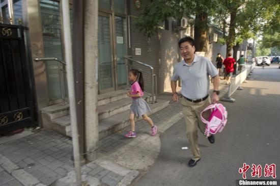 资料图:一名即将要迟到的小学生在家长的护送下跑步将孩子送来学校。中新社发 崔楠 摄